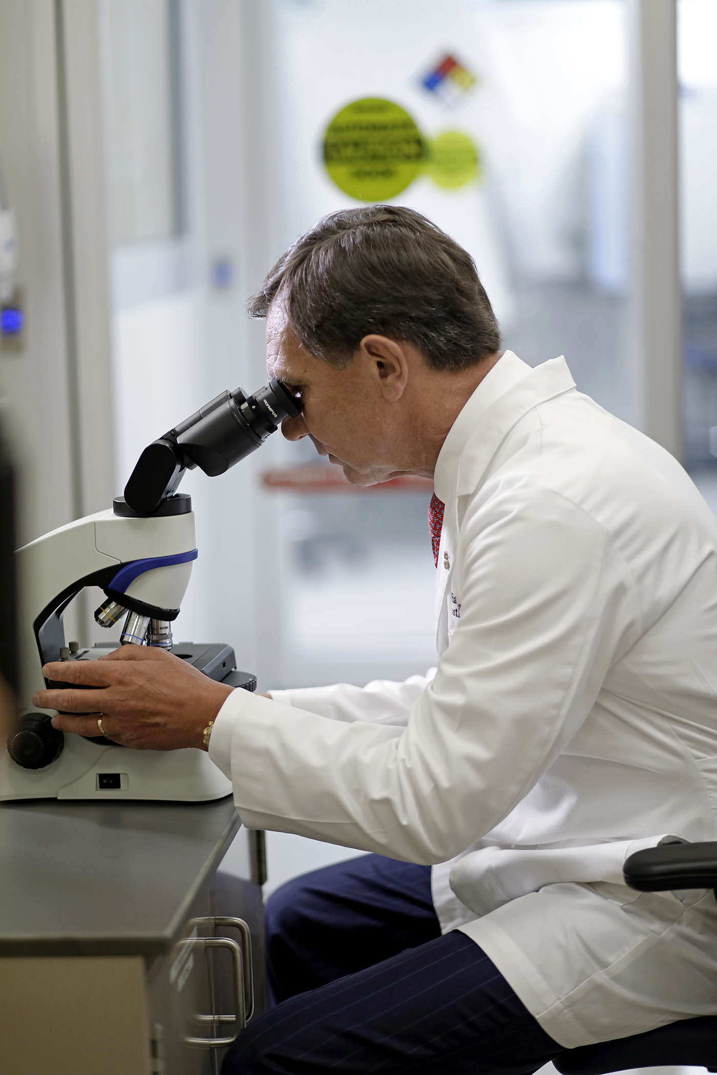 Dr. Guenther Koehne, Miami Cancer Institute, looking through microscope